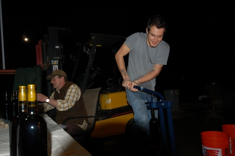 Bob tops off the bottles while Tylor operates the corker.