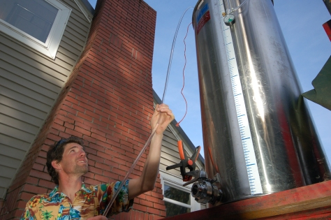 Nathan runs a siphon hose out of an elevated, stainless steel drum holding the filtered wine.