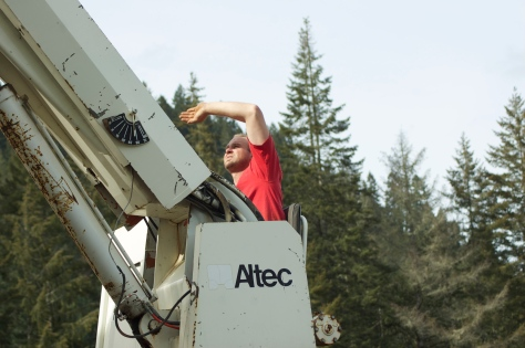 Nick shields his eyes against the sun as he maneuvers the form into place over the top of the silo.