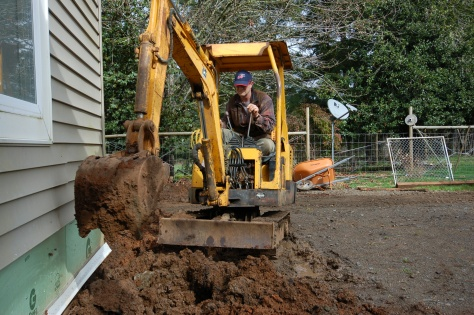 Bob digging up the front porch in February, thereby guaranteeing three months of endless rain.